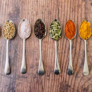 row of spoons containing different spices